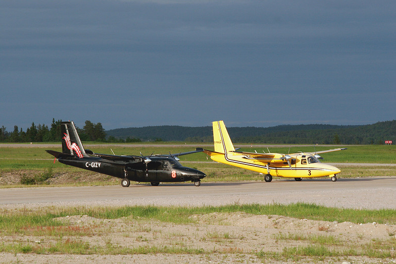 A Aero Commander 500B and a Aero Commander 500S sit on the taxiway at Dryden. The yellow aircraft has since being painted white, and the black one is scheduled to be repainted as well.
