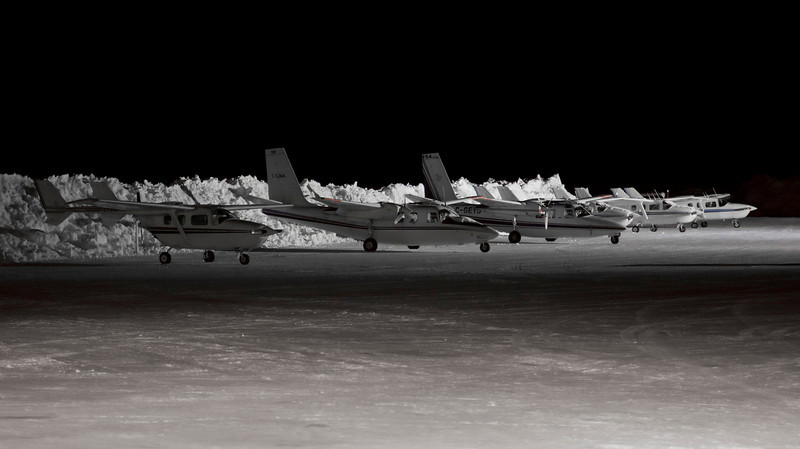 60 of 365 (Waiting For Spring)<br /> <br /> Several aircraft from Discovery Air waiting for spring to arrive so they can go out looking for forest fires. <br /> <br /> A not quite black and white image, shot at ISO 2500, 1/6th of a second at F4.0. The camera was placed on top of a GPU (ground power unit) to steady it for the longer shutter speed.