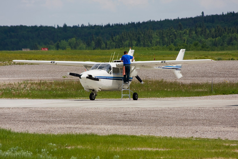 Checking the fuel levels on C-GWDU, a Cessna 337B.