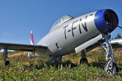 """Sandefjord Airport Torp (TRF) on September 13, 2013. Royal Danish Air Force Republic F-84G-6-RE Thunderjet """"A-803"""" (cn 51-9803). Put on display near the fire station. This aircraft is repainted to represent Royal Norwegian Air Force F-84G-16-RE """"FN-T"""" (cn 51-10634) from 331 Squadron."""