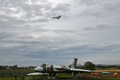 To the delight and sadness of the gathered people at East Fortune, XH558 passes over the former airfield.  The former Control Tower is visible to the left of the nose of XM597. XH558 was restored to flying condition by the Vulcan to the Sky Trust. The first post-restoration flight, which lasted 34 minutes, took place on 18 October 2007.