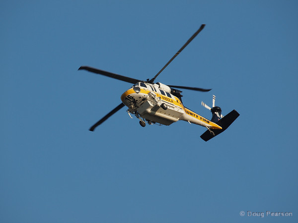 Copter 16, one of the Los Angeles County Fire Department Fire Hawk Helicopters does a quick orbit so they can drop the second half of their water on a spot fire at Sunflower IC.