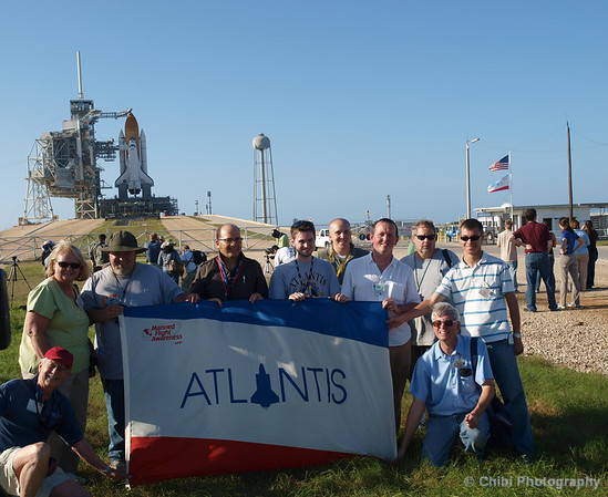 Photographers hold a flag for Space Shuttle Atlantis, Orbiter Vehicle-104 (OV-104) seen behind them on Launch Pad 39 A preparing for the Shuttle Transportation System (STS-132) mission to the International Space Station. May 13, 2010