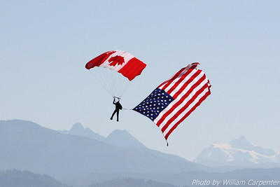 A member of the Canadian Forces Skyhawks Parachute Team tows the flag of the United States flag at the 2010 Abbotsford International Air Show.