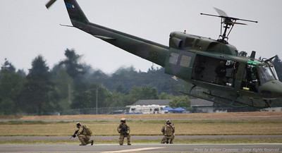 Troops are deployed from a Huey during a simulated field assault.