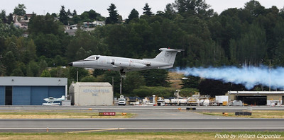 An aerobatic Learjet, complete with smoke system, takes off.
