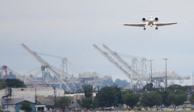 An inbound jet with Harbor Island in the background.