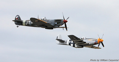 The Spitfire and the Mustang fly a formation pass down the runway.