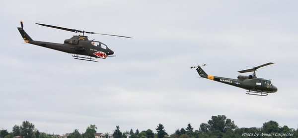 An AH-1 Cobra and a UH-1 Huey, both from the Olympic Flight Museum, take off and head to the lake.