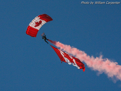 Skydivers from the Canadian Forces Skyhawks tow the Canadian and American flags during the opening ceremonies.