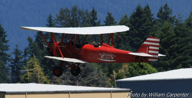 A 1930's biplane takes off with guest riders on board.
