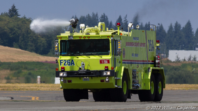 The airport fire department showing off for the crowd.