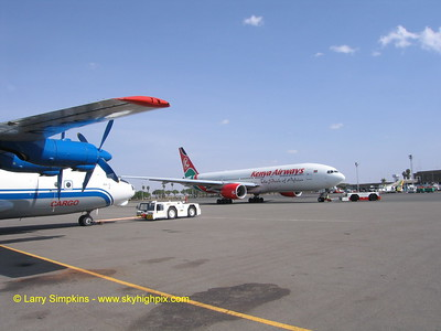 Kenya Airways, Boeing 777 being pushed back for departure at Nairobi, Africa. Antonov An-12 freighter on left.