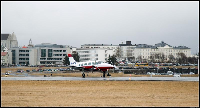 Íslenskt heilbrigðiskerfi í hnotskurn. Sjúkraflugvél lendir á Reykjavíkurflugvelli. Í baksýn er sjúkrahúsið sem sjúklingurinn fer líklega á.