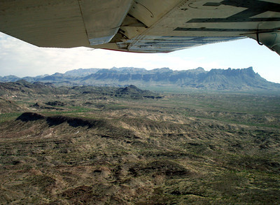 CHISOS MOUNTAINS I couldn't resist taking a shot of the Chisos Mountains off in the distance. If you'll notice, Curtis flies with a small amount of flaps extended. This puts the airplane in a slightly nose-down attitude to make it easier to see ahead. Pretty smart!