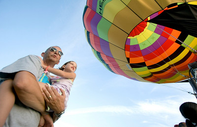 Kevin Hardin of Sycamore and his daughter Emma, 5, watch as members of the BUB Hot Air Balloon Team take control of a hot air balloon that landed near Bethany Road in Sycamore on Monday evening.