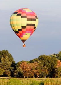 A hot air balloon descends near an open field next to Bethany Road in Sycamore on Monday, August 11.  The balloon, piloted by Rick Poe of Sycamore, also carried Robin Lovejoy and Wendy Harries, both of Sycamore.  Lovejoy and Harries were given a gift certificate for the balloon ride by Ed Getzelman of Hampahire last year.  It was the first balloon ride for both women.