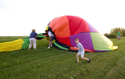 Aaron Stone, 8, of Sycamore runs near the envelope of a hot air balloon shortly after it landed near Bethany Road in Sycamore on Monday evening.  The balloon was piloted by Rick Poe (center) of the BUB Hot Air Balloon Team in Sycamore.  Poe's wife Sally (left) is the crew chief for the team.