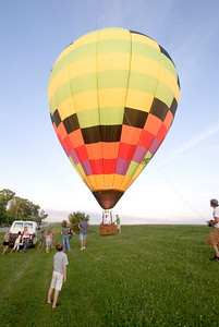Dozens of Sycamore-area residents gather around a hot air balloon that landed near an open field next to Bethany Road in Sycamore on Monday, August 11.  The balloon, piloted by Rick Poe of the BUB Hot Air Balloon Team in Sycamore, also carried Robin Lovejoy and Wendy Harries, both of Hampshire.  Lovejoy and Harries were given a gift certificate for the balloon ride by Ed Getzelman of Hampahire last year.  It was the first balloon ride for both women.