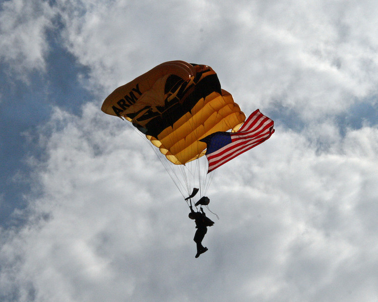 One of the Army Golden Knights bringing in the flag to start the air show.