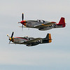 """Top aircraft - P-51C """"Red Tail"""" Mustang flown by the Minnesota Wing of the Commemorative Air Force and painted in the colors of the 332nd Fighter Group in memory of the Tuskegee Airmen of WWII. <br /> <br /> Bottom Aircraift - P-51D """"Gunfighter"""" flown by the Great Plains Wing of the Commemorative Air Force and painted in the colors of the 343rd Fighter Squadron of the 8th Air Force during WWII."""