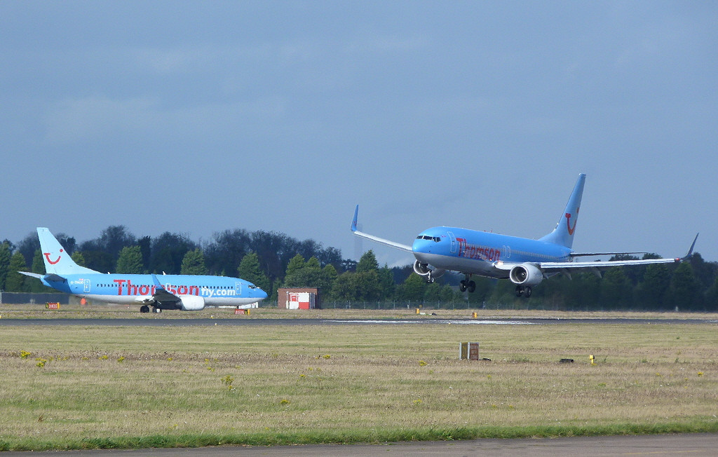 Thomson Airways 737-800 G-FDZU contends with a stiff breeze as G-THOO waits to line up.<br /> By Clive Featherstone.