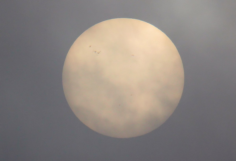 A low cloud bank drifting across the sun gave the opportunity to photograph the large group of sunspots in the top left hand quarter of the disc. Three smaller spots are also visible, two below the central area and one above.<br /> By Jim Calow.