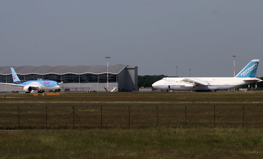 Thomson Airways 787-800 G-TUIC taxis past the terminal with An-124 UR-82009 parked on stand 8A.<br /> By Jim Calow.