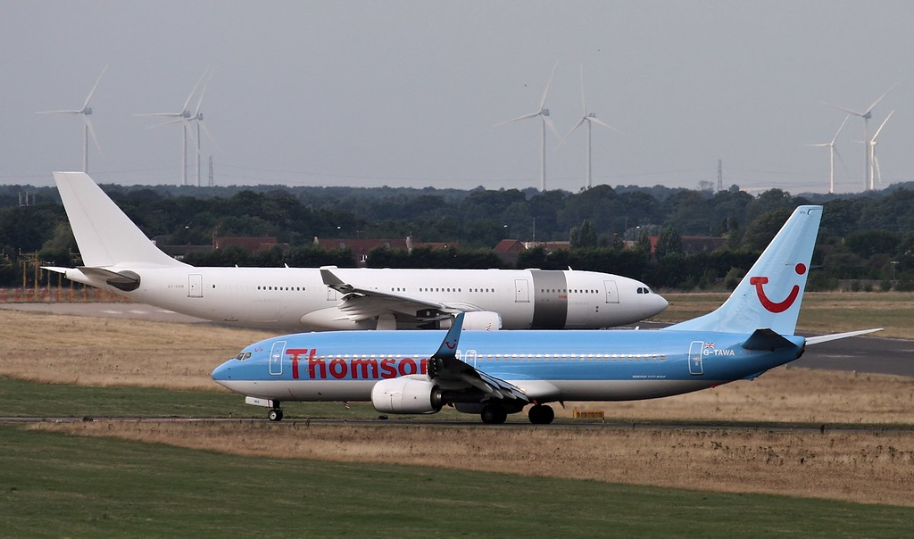 A330 A7-HHM about to enter the runway via taxiway 'Charlie' as Thomson 737 G-TAWA exits the runway via taxiway 'Bravo'.<br /> By Jim Calow.