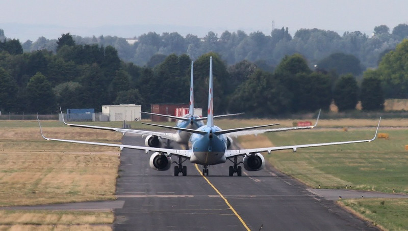 Departing Thomson Airways 737-800 G-FDZE leads arriving G-TAWA along taxiway 'Alpha'.<br /> By Jim Calow.
