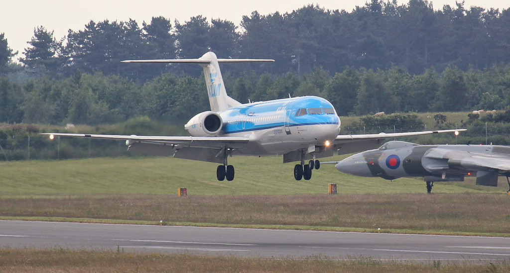 KLM Fokker 70 PH-WXD was still in the circuit early afternoon. In the background XH558 waits to depart on a crew training flight.<br /> By Jim Calow