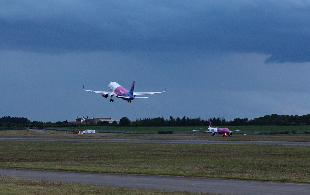Wizz Air A320 HA-LYQ lifts off as HA-LPO taxis to the terminal.<br /> By Clive Featherstone.