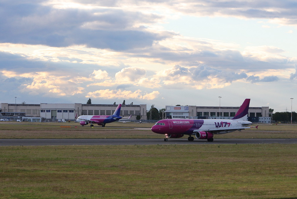 Wizz Air A320 HA-LYQ taxis to stand as HA-LPS arrives.<br /> By Clive Featherstone.