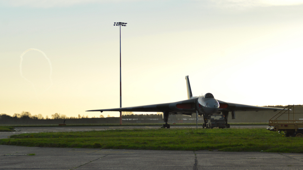 Vulcan XH558 waits on Stand 16 whilst the The Red Arrows make patterns in the sky.<br /> By Kev Barwell.