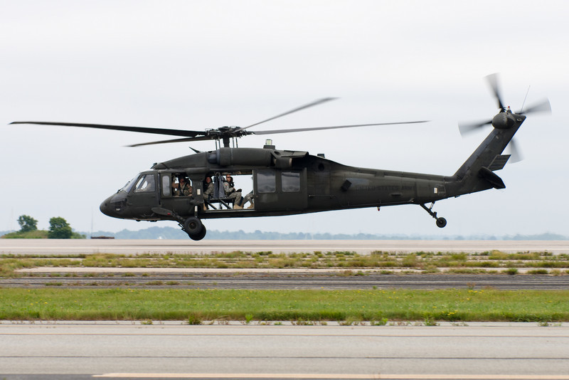 The Blackhawk buzzes the runway with soldiers waving.