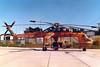 """Sikorsky S-64E Skycrane (Erickson Air-Crane """"Olga"""") [1968] N6962R<br /> Torrance Municipal Airport, Torrance, California - early 1970s<br /> <br /> This rather leggy heavy-lift helicopter design began as the Sikorsky S-64 Skycrane, the civilian version of the US Army's CH-54 Tarhe, a multi-use helicopter. Interchangeable containers, called Universal Military Pods, can be used to transport either combat troops or stretcher cases, but they can also be fitted out as field hospitals, communications centers, or command posts. It's 20,000-pound payload capacity earned it its name """"Skycrane."""" These helicopters can also be fitted with 2,650-gallon fire retardant tanks for use in wildland fire suppression and are quite capable in that role. This Skycrane was one such tanker.<br /> <br /> Built in 1968, this helicopter was registered as N6962R, and was substantially damaged on July 3, 1970, at Union City, Tennessee. After placing a load at the roof of a building, both engines ingested plastic causing flameouts and complete loss of power. The following forced landing ended on top of the just-released load and there was a post-impact fire.<br /> <br /> Sometime after being rebuilt, the aircraft was registered in Ecuador as HC-CAT. Upon its return to the USA, it was registered again as N6962R. Using a detachable 2,650-gallon tank, the aircraft is often used as a firefighter, and is listed as """"Tanker 747"""".<br /> <br /> [The last two paragraphs courtesy of 1000aircraftphotos.com]"""