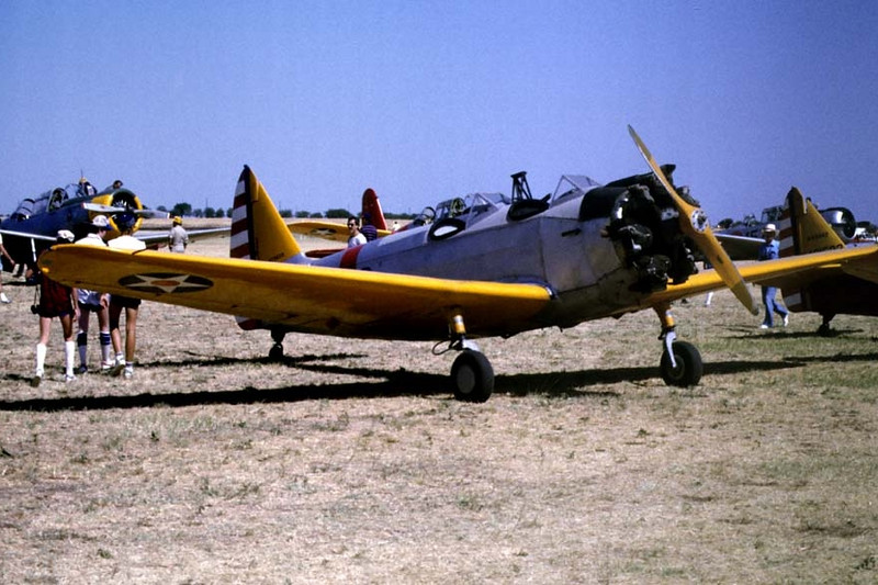 Fairchild M-62A/PT-23 [1944] N73608 (c/n FV-676)<br /> Confederate Air Force Airshow, Denton, Texas - July 1984<br /> <br /> There were never any production model PT-23s painted in pre-war colors, as you often see them decked out. In fact, almost all PT-23s were painted an overall silver with the star-and-bar insignia. None ever carried the red, white, and blue rudder markings.