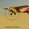 light 2-seater aircraft in red and orange flying out of the sunset