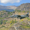 A tiger II fighter jet coming in to land wtih mountains and vineyards in the background