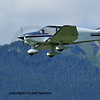 a light 4 seater aircraft with cantered wings and a wooden airframe with mountains in the background