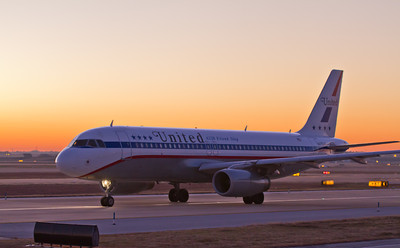 A United Airbus A320 taxies by spot 24 on taxiway Kilo at DFW. The sun is rising in the East. I was in the right seat on a new Captain's IOE.