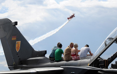 People watch a performance while sitting on the German Air Force Tornado aircraft during Saturday's Colorado Sport International Airshow at Rocky Mountain Metropolitan Airport. August 28, 2010 staff photo/David R. Jennings