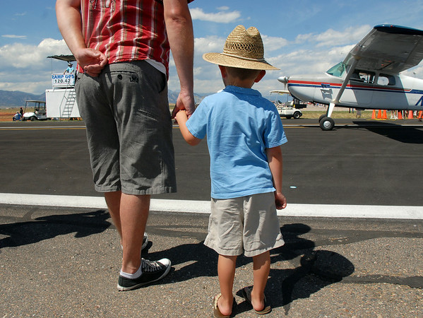 A father and son wait for and airplane to taxi past during Saturday's Colorado Sport International Airshow at Rocky Mountain Metropolitan Airport.<br /> August 28, 2010<br /> staff photo/David R. Jennings