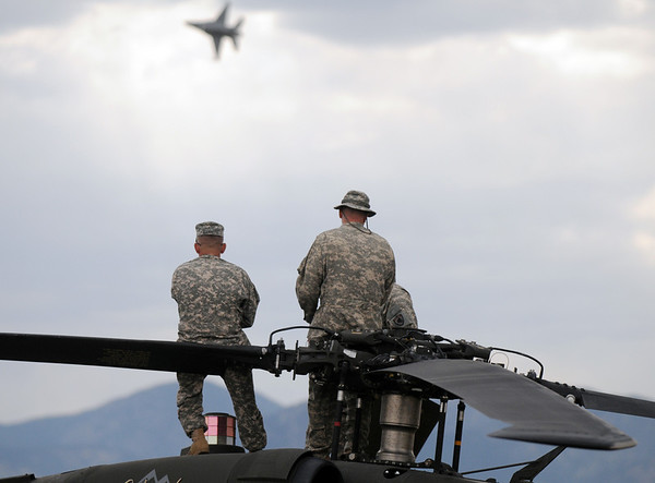 Members of the Colorado National Guard sit on their Black hawk helicopter watching the F-16 Viper preform during Saturday's Colorado Sport International Airshow at Rocky Mountain Metropolitan Airport.<br /> August 28, 2010<br /> staff photo/David R. Jennings