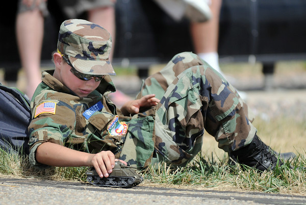 Civil Air Patrol cadet Sasha Witvliet, 12, plays with a toy tank while at his post during Saturday's Colorado Sport International Airshow at Rocky Mountain Metropolitan Airport.<br /> August 28, 2010<br /> staff photo/David R. Jennings