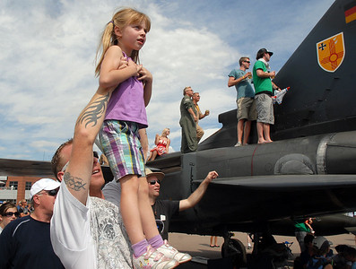 Steve Gade holds his daughter Nataliya, 5, of Broomfeild, in the air to watch an aircraft performance during Saturday's Colorado Sport International Airshow at Rocky Mountain Metropolitan Airport. August 28, 2010 staff photo/David R. Jennings