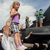 Steve Gade holds his daughter Nataliya, 5, of Broomfeild, in the air to watch an aircraft performance during Saturday's Colorado Sport International Airshow at Rocky Mountain Metropolitan Airport.<br /> August 28, 2010<br /> staff photo/David R. Jennings