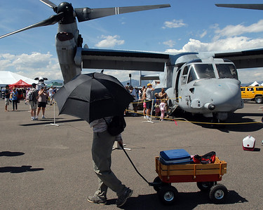 A person, carrying an  umbrella and pulling a wagon, walks by the US Marine Corps MV-22 Osprey on display during Saturday's Colorado Sport International Airshow at Rocky Mountain Metropolitan Airport. August 28, 2010 staff photo/David R. Jennings