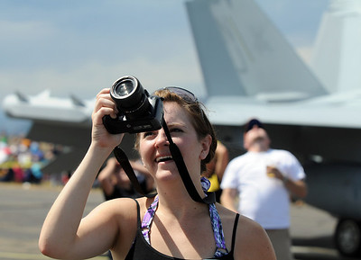 Desi Lauwers, of Lakewood, takes pictures of an airplane performance during Saturday's Colorado Sport International Airshow at Rocky Mountain Metropolitan Airport. August 28, 2010 staff photo/David R. Jennings