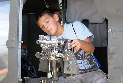George Robledo, 12, of Arvada, checks out a machine gun on the Colorado National Guard's Black Hawk helicopter during Saturday's Colorado Sport International Airshow at Rocky Mountain Metropolitan Airport. August 28, 2010 staff photo/David R. Jennings